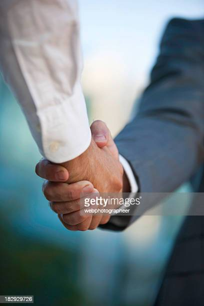Businessmen shake hands against blurred background