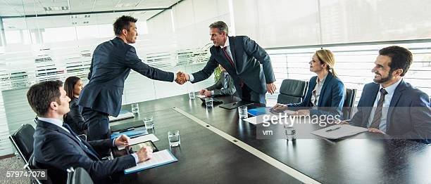 Businessmen shake hands over a table