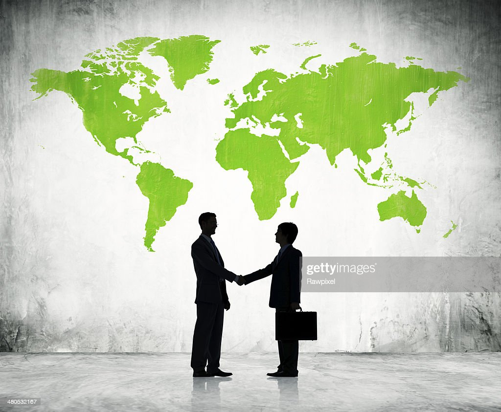 Businessmen shake hands with green land background : Stock Photo