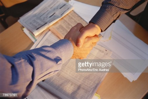 Businessmen shaking hands across table, cropped view, financial pages of newspapers in background