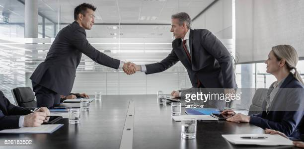 Hommes d'affaires se serrant la main après la signature du contrat