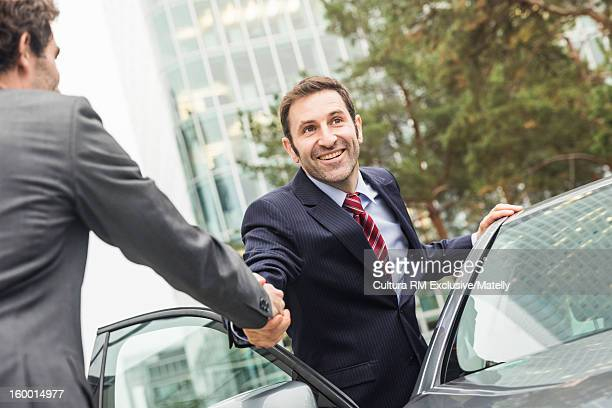 Businessmen shaking hands by car
