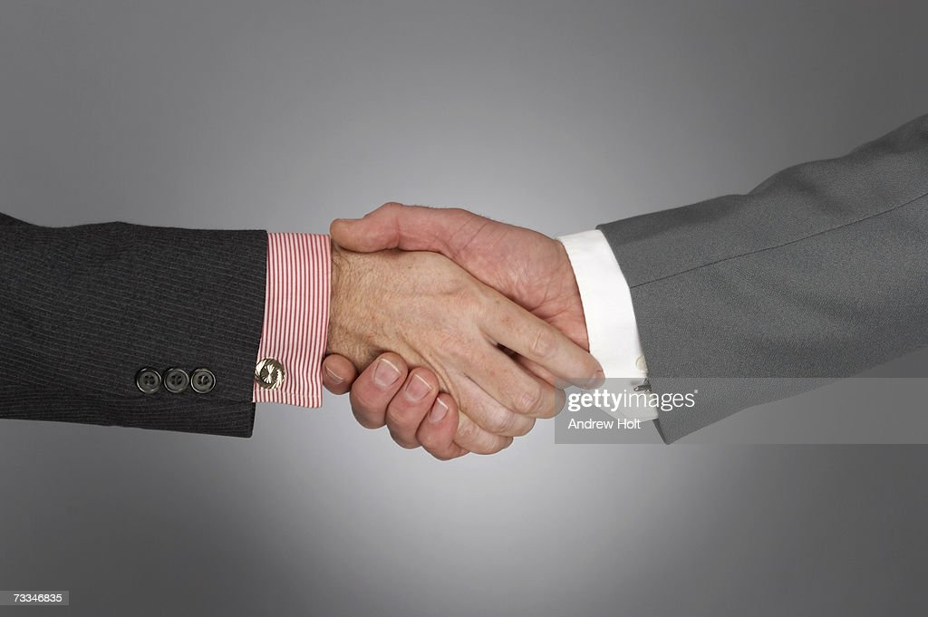 Businessmen shaking hands, close-up : Stock Photo