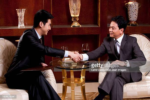 Businessmen shaking hands in a luxurious room