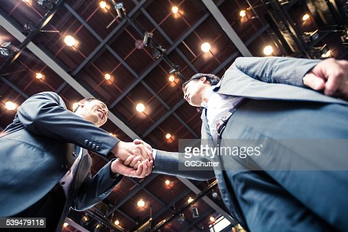 Businessmen shaking hands in agreement over a successful acquisition.
