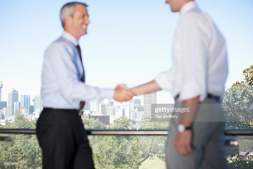 Businessmen shaking hands in cafe : Stock Photo