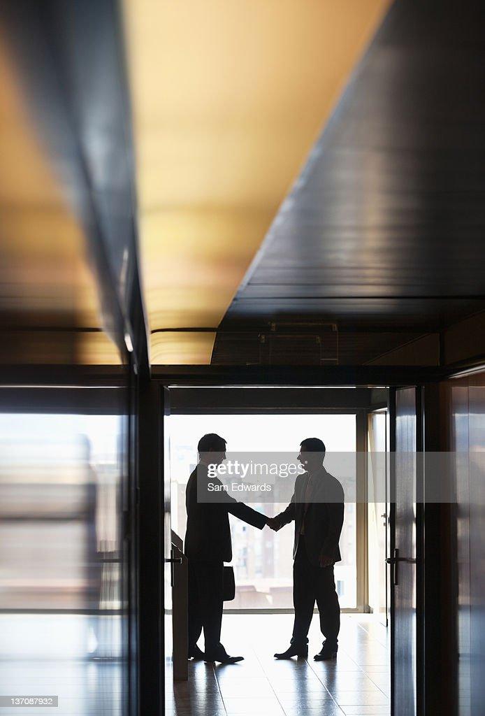 Businessmen shaking hands in corridor : Stock Photo