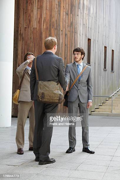 Businessmen shaking hands in courtyard