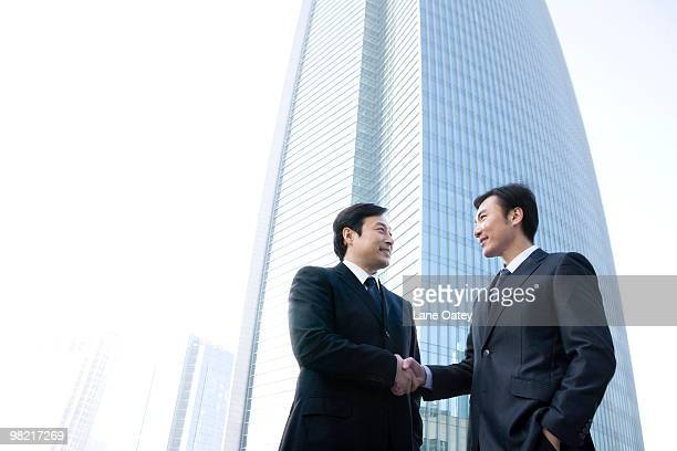 Businessmen shaking hands in front of tall building