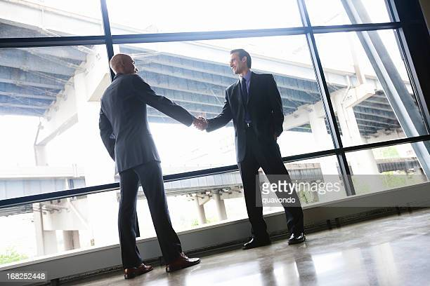 Businessmen Shaking Hands in Glass Office, Copy Space