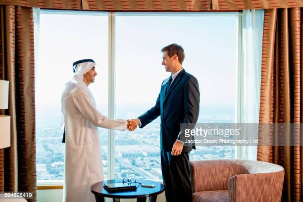 Businessmen shaking hands in hotel room