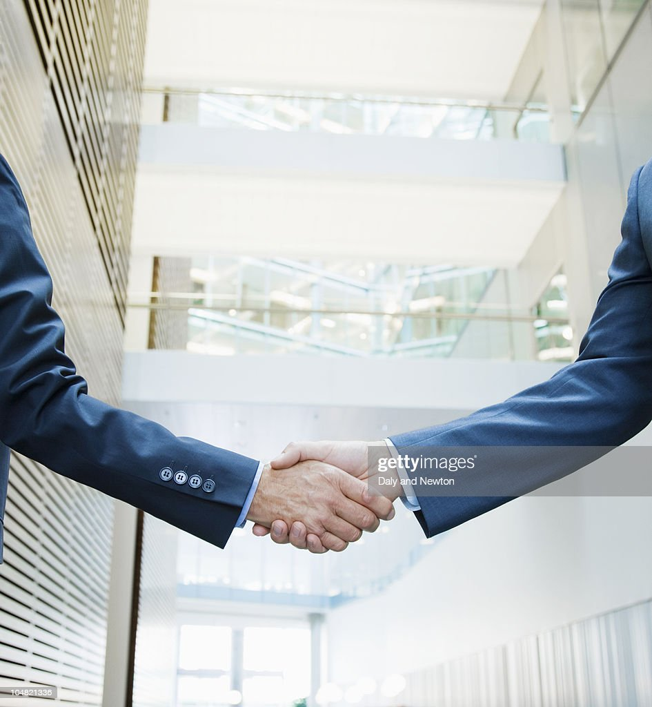 Businessmen shaking hands in lobby