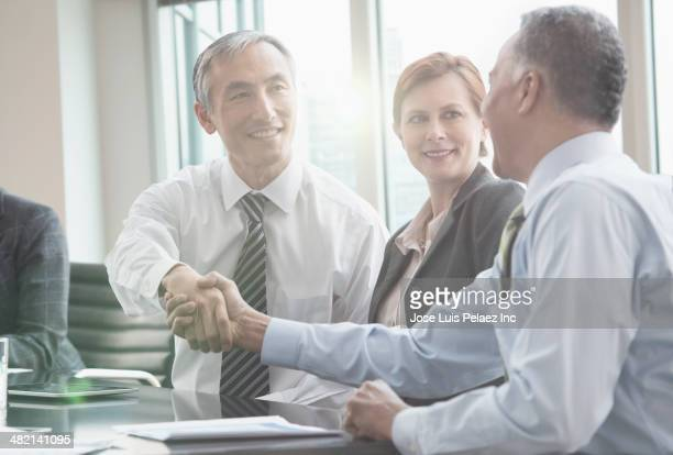 Businessmen shaking hands in meeting