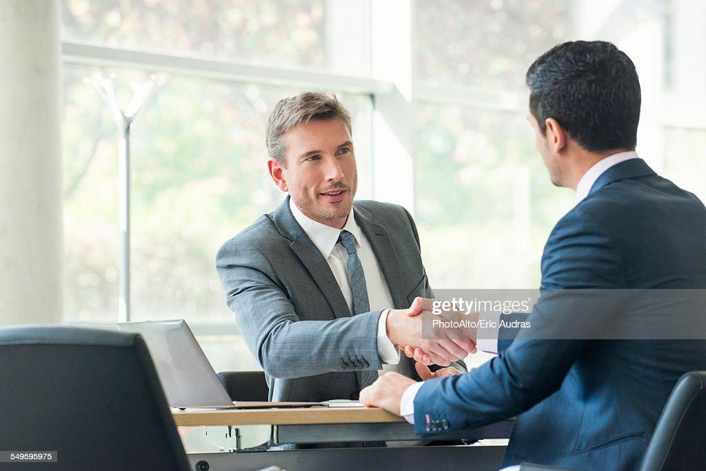 Businessmen shaking hands in meeting : Foto stock