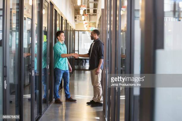 Businessmen shaking hands in office hallway