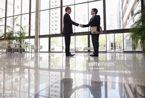Geschäftsleuten beim Händeschütteln im Büro-lobby