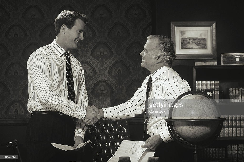 Businessmen shaking hands in office or boardroom : Stock Photo