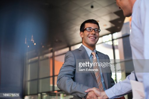 Businessmen shaking hands in office : Stock Photo