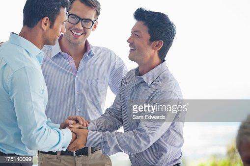 Businessmen shaking hands in office