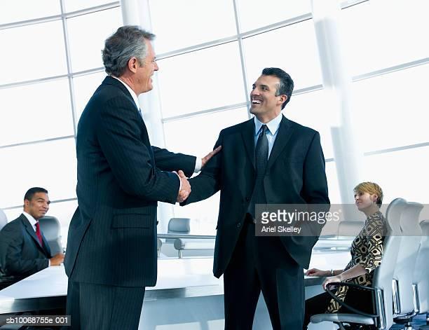 Businessmen shaking hands in office, smiling