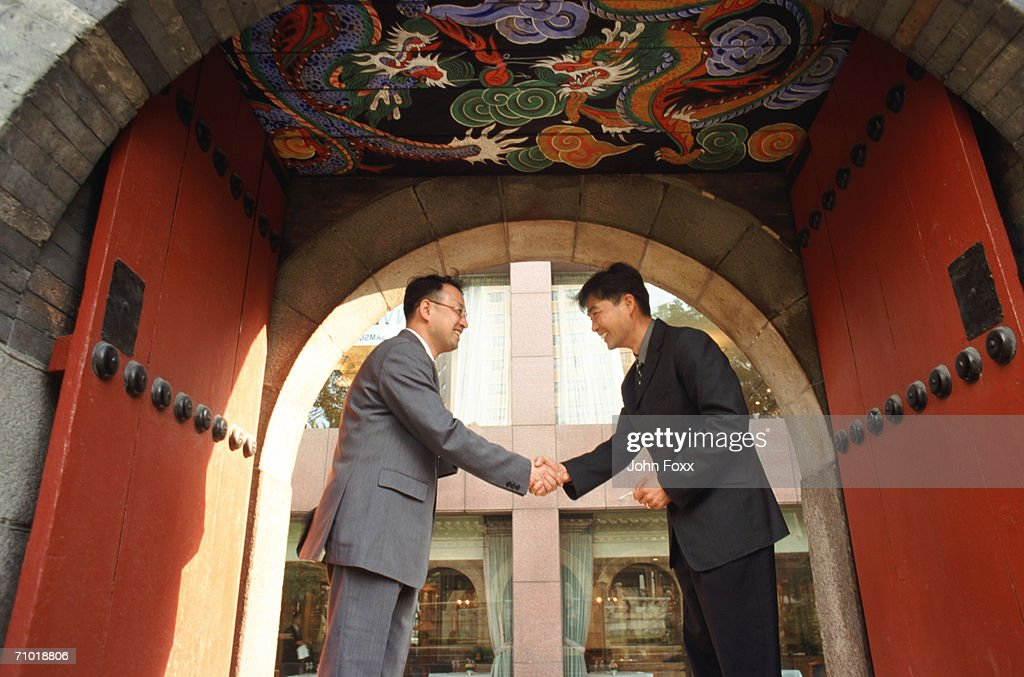 Businessmen shaking hands, low angle view : Stock Photo