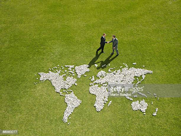 Businessmen shaking hands near world map made of rocks