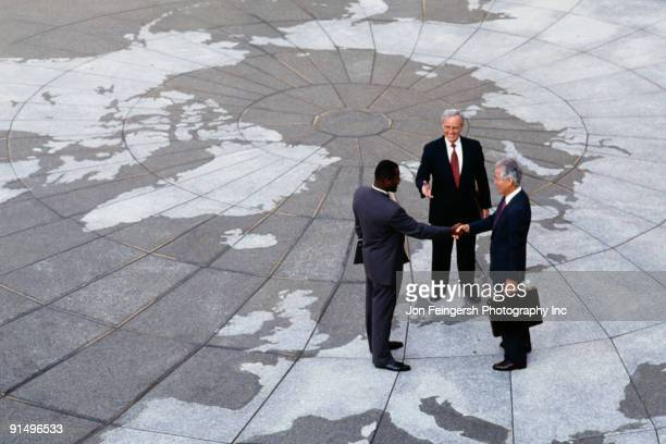 Businessmen shaking hands on map of globe