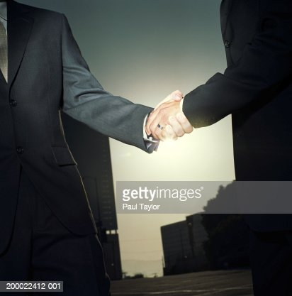 Businessmen shaking hands outdoors, sunset