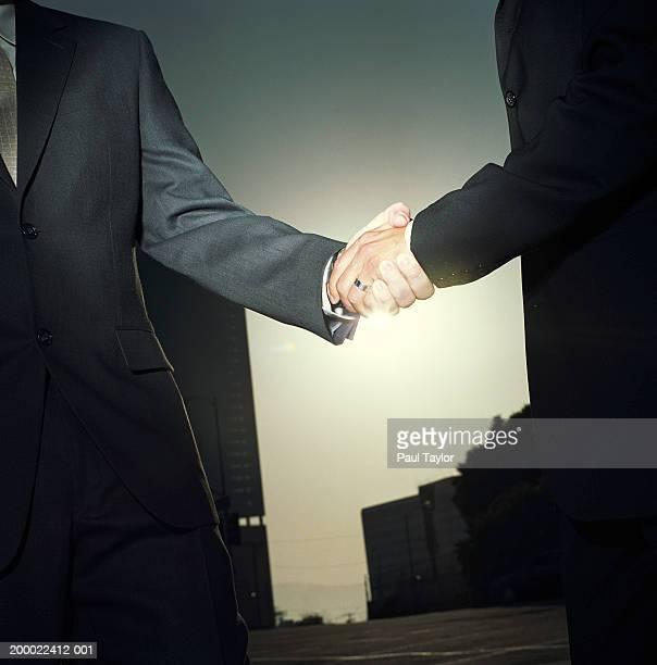 Businessmen shaking hands outdoors, sunset