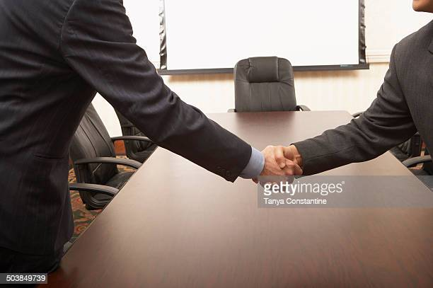 Businessmen shaking hands over conference table