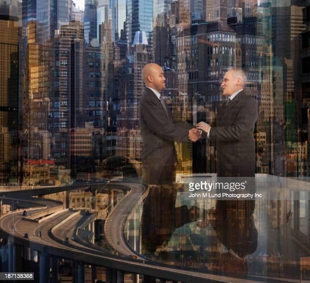 Businessmen shaking hands over skyscrapers