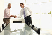 Businessmen Shaking Hands over Table