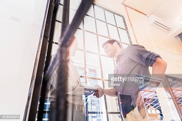 Businessmen shaking hands seen through glass wall