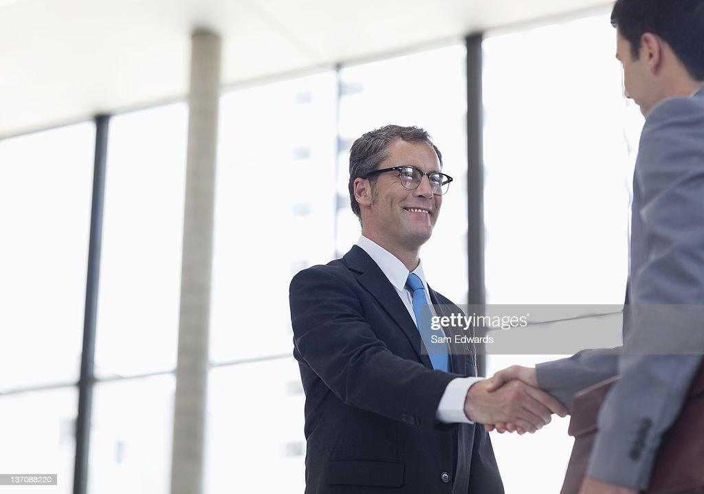 Businessmen shaking hands together : Stock Photo