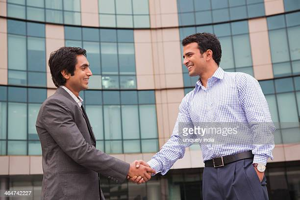 Businessmen shaking their hands and smiling