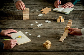Businessmen sharing ideas concept. Close-up full frame image with hands of four people over rough wooden table, with dominoes effect, drawing light bulb, puzzle pieces and other conceptual stuff.