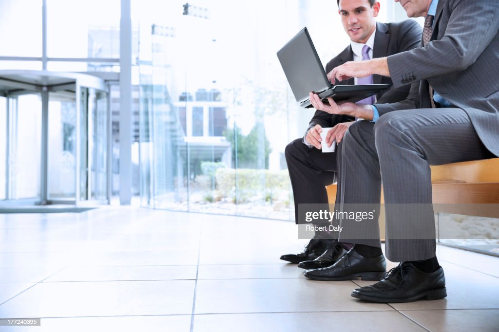 Businessmen sharing laptop in lobby : Stock Photo