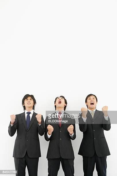 Businessmen shouting, clenching fists, portrait
