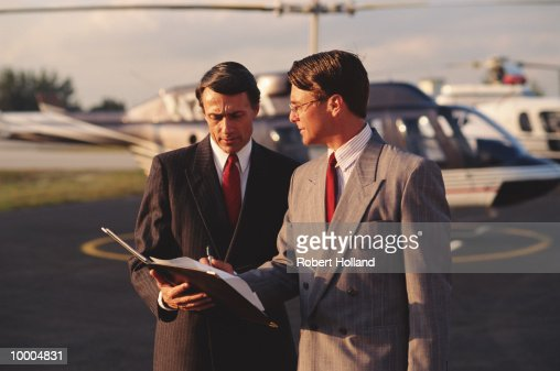 Businessmen signing papers near helicopter : Stock Photo