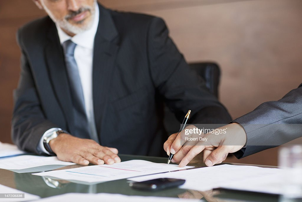 Businessmen signing paperwork : Stock Photo
