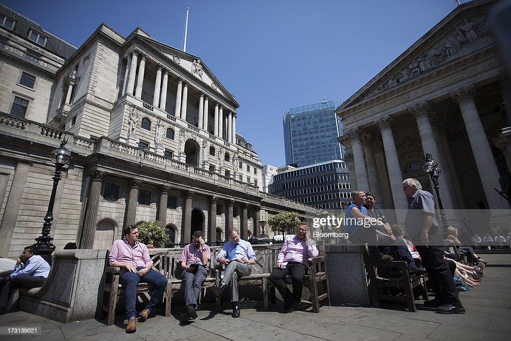 Businessmen sit outside the Bank of England, left, and the Royal Exchange in London, U.K., on Monday, July 8, 2013. Britain's economy could be in line for a period of 'strong catch-up growth' once it gets through the current weakness, according to Capital Economics Ltd. Photographer: Simon Dawson/Bloomberg via Getty Images