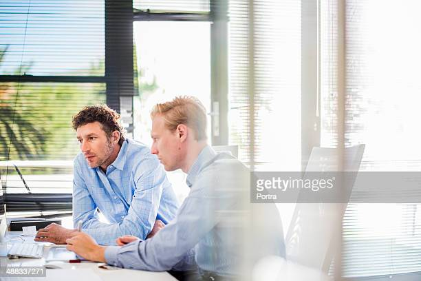 Businessmen sitting at desk in office