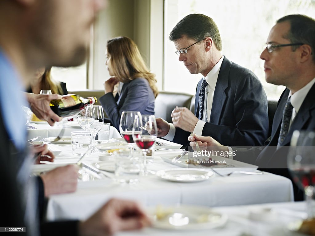 Businessmen sitting at table in restaurant : Stock Photo
