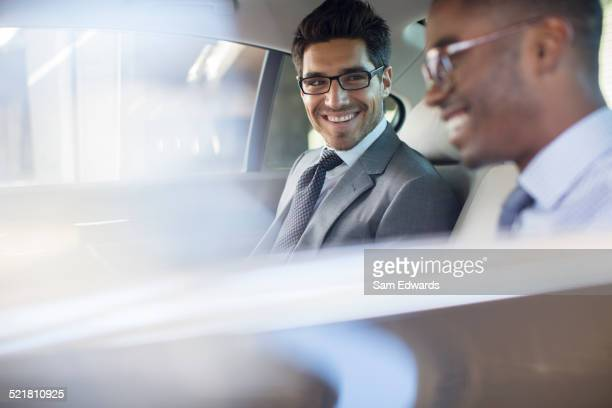 Businessmen sitting in car back seat