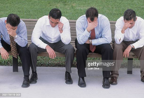 Businessmen sitting on  bench, heads down with hands on foreheads