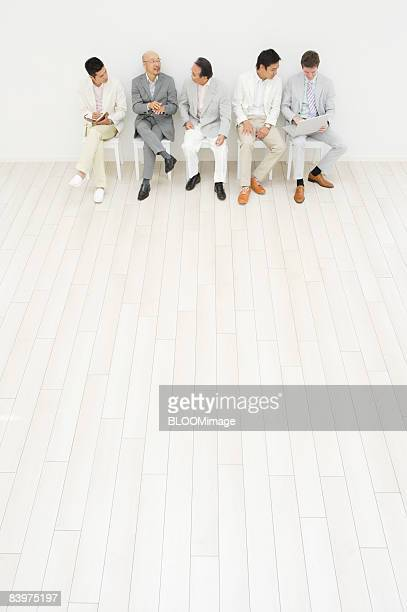 Businessmen sitting on chairs in row against wall, enjoying talking