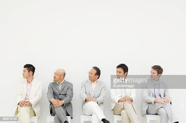 Businessmen sitting on chairs in row against wall, looking left, legs crossed
