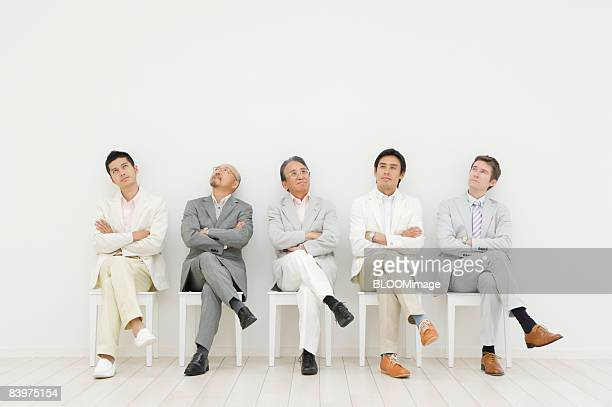 Businessmen sitting on chairs in row against wall, with legs crossed, arms folded, thinking