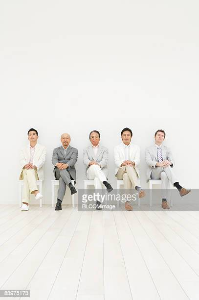 Businessmen sitting on chairs in row against wall, with legs crossed