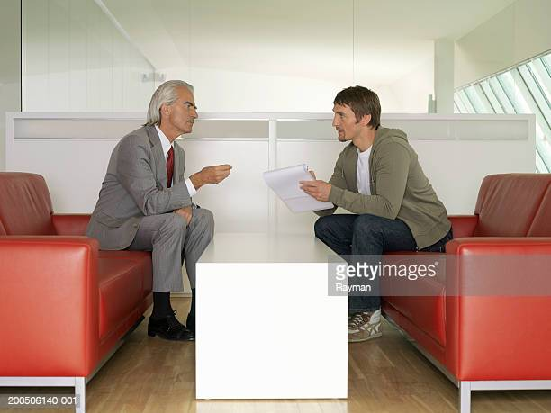 Businessmen sitting on sofas in discussion
